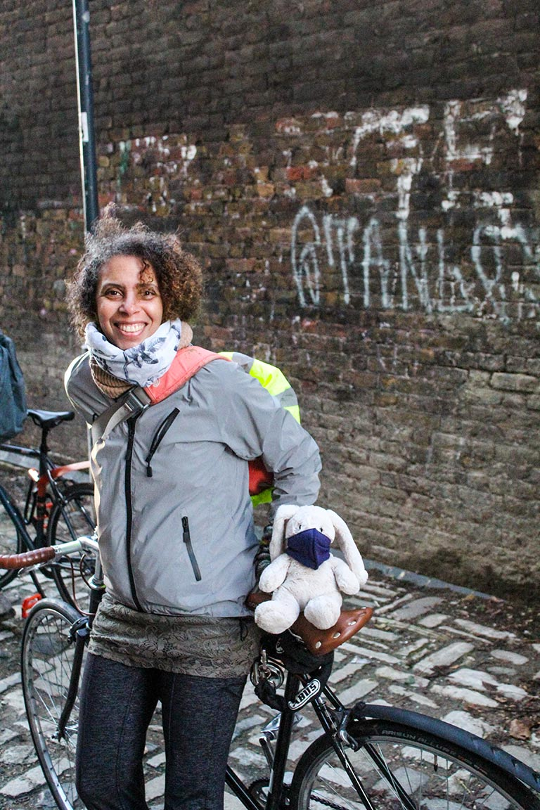 Adesola Akinleye leaning against a bike, smiling