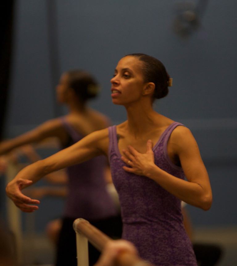 Adesola standing with arms out demonstrating a dance move while teaching.
