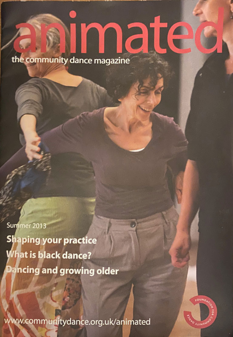 Magazine cover - two women smiling and dancing back to back. Animated Summer 2013 issue