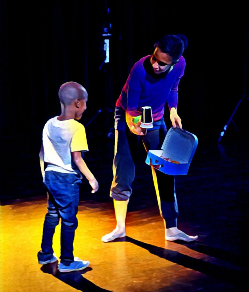 dancer shows a cup to small boy.
