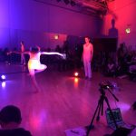 Two dancers in pink light. One dancer balancing on one leg, the other watching her.